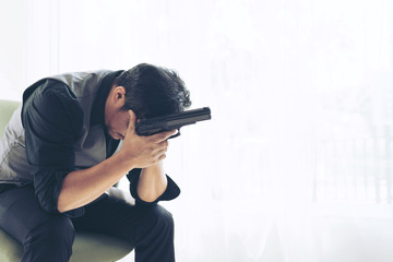 business man is stressed from work , Holding a gun in hand maybe think of suicide, copy space  - business concept