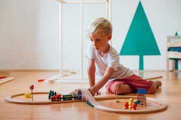 Little Boy Playing With Toy Railroad At Home