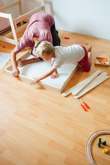 Father And Son Working On Carpentry At Home