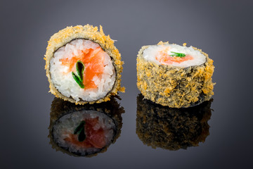Hot roll with salmon tempura on black with reflection