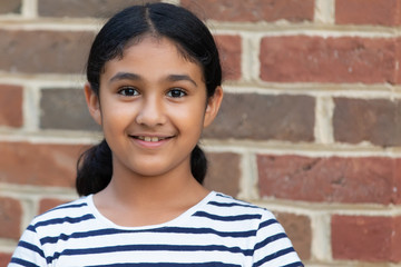 Outdoor Portrait of a Smiling Little Girl Against a Brick Background