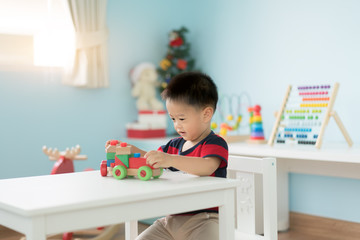 Adorable Asian Toddler baby boy sitting on chair and playing with color wooden train toys at home..
