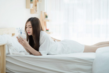 A beautiful young woman holding cup of coffee and lying on bed comfortably and happily. Happy morning. Portrait of a smiling pretty girl relaxing in white bed.