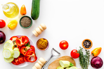 Cooking vegetable stew concept. Fresh vegetables squash, bell pepper, tomato, spices and cutting doard on white background top view copy space
