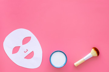 Cosmetic product for cleansing skin. Facial mask, cream and brush on pink background top view space for text