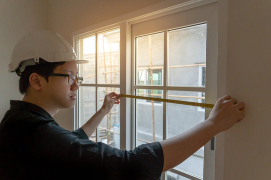 Young Asian engineer or worker with safety helmet and eyeglasses using tape measure for measuring window at construction site. House builder concept. Architecture and engineering of housing project