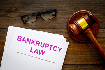 Words bankruptcy law written on the documents near judge gavel on dark wooden background top view