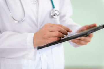 Closeup of female medical doctor is using tablet for physical patient examination