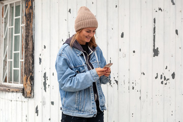 Stylish young woman in denim coat, knitting hat and scarf using smart phone near the sea and lighthouse at cold season. Female looking into mobile device at winter day by the ocean.