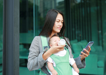 Business woman working by telephone with carrying her infant and feeding her child's by milk bottle. Busy mother hurrying in the morning with baby.