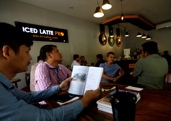 A man reads a book at a coffee shop in Phnom Penh