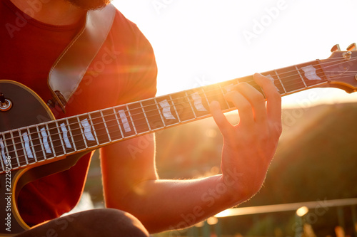 hands of guitarist playing electric guitar chords outdoors, evening ...