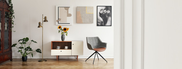 Panorama of posters and grey armchair in bright living room interior with copy space. Real photo