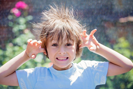 Cute little boy with static electricy hair, having his funny portrait taken
