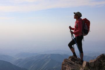 Young woman hiker with backpack standing on top of the mountain