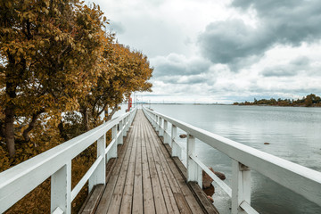 Wooden bridge along the shore of the Baltic Sea, in the capital of Finland, Helsinki, autumn landscape