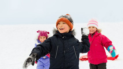 childhood, leisure and season concept - group of happy little kids in winter clothes playing outdoors