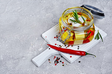 Marinated feta cheese with olive oil and spice of red chili pepper and rosemary in glass jar on white wooden board