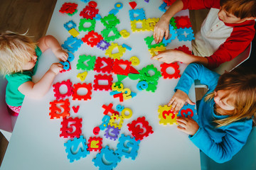 kids playing with number and shapes puzzle