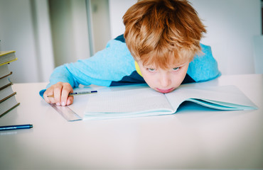 little boy exhausted tired of doing homework,overload