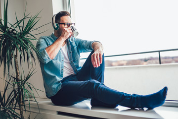 Photo in of pleased man looking through window and listening to music using wireless earphones while drinking cup of coffee