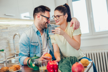 Cute couple eating breakfast in the kitchen and having a good time.