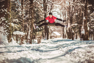 Young runner in sportswear jumping on snow covered winter road near the forest.