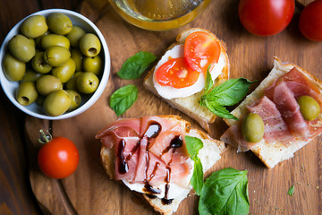 Appetizing bruschettes with jamon, tomatoes, basil, mozzarella, olives and oil on a dark wooden board