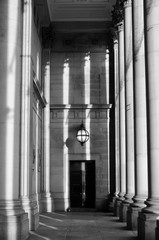 monochrome tall classical columns stone walls and door in sunlight and shadow in the portico of leeds town hall in west yorkshire
