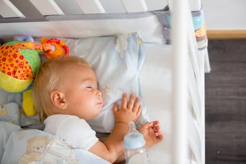 Cute little baby boy, sleeping with bottle with formula milk