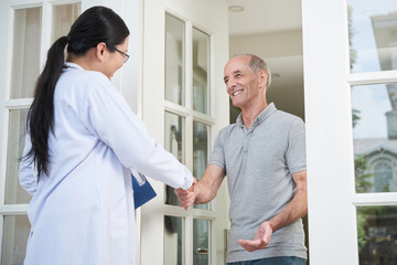 Female doctor with clipboard shaking hand of senior man during home visit while entering house