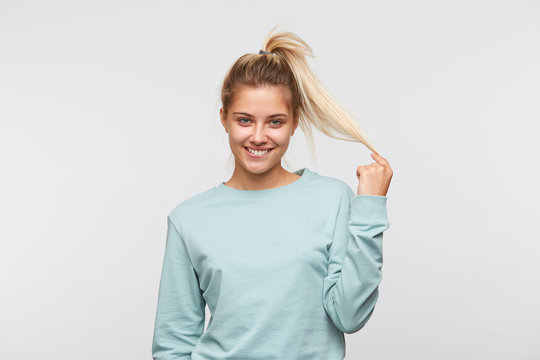 Portrait of smiling playful young woman with blonde hair and ponytail wears blue sweatshirt biting her lip and and flirting isolated over white background