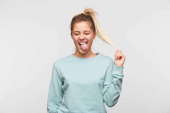 Closeup of funny joyful pretty young woman with blonde hair, closed eyes and ponytail wears blue sweatshirt shows tongue and having fun isolated over white background
