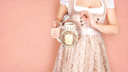 Woman with traditional cup of beer in front of her decollete, she is wearing Bavarian Tracht, a Dirndl Fototapete