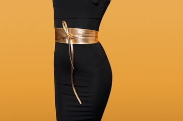 female figure in a black dress with a gold belt. Diet concept