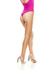 long pretty female legs, pink sweamsuit and sandals with high heels from behind on white background