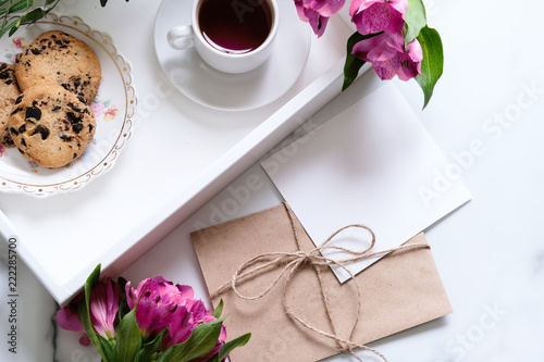 Marble desk with cup of coffee, pink flowers, postcard, kraft envelope, twine, cotton branch, oat cookies, invitation card with copy space for text. Flat lay, top view. Woman's day or mother's day.