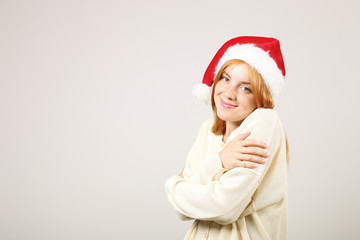 Close up portrait of beautiful redheaded young woman wearing Santa Claus hat & white sweater with satisfied facial expression. Cute female celebrating New Year. Copy space, isolated on gray background