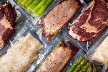 Meat and asparagus vacuum sealed on black table, from above