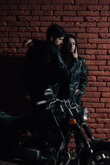 sexy couple. sexy couple with motorbike. sexy couple on red brick wall background. sexy couple in love. confident mechanic.