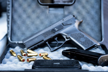 Close up view of bullets and handgun. Small black pistol next to a 9 mm bullets and a magazine. Shallow depth of field.
