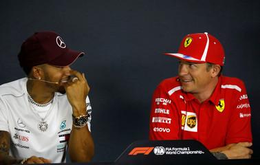Mercedes' Lewis Hamilton and Ferrari's Kimi Raikkonen react during a news conference in Singapore
