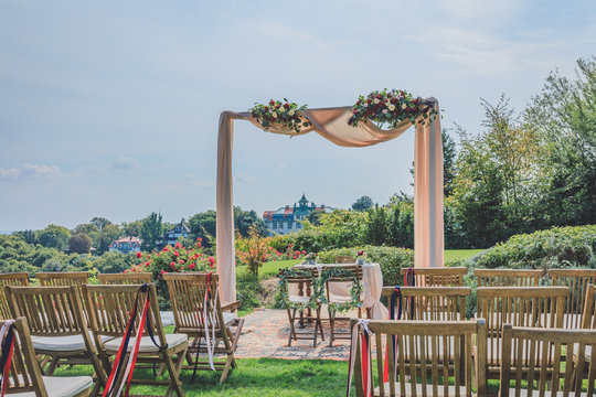 Beautiful decorated table and rows of embellished chairs with decorative ribbons for festive event in the vineyard