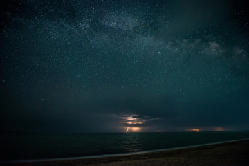 Starry night with thunderstorm and lightning over the sea