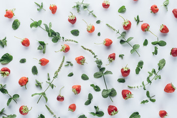 top view of fresh strawberries with mint leaves on white tabletop