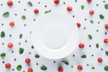 top view of ripe strawberries around empty plate on white surface