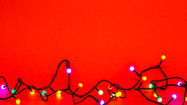 Christmas lights over red background. Colorful border with empty copy space for text.