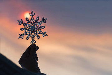 Female hands in a knitted mittens with sparkling huge snowflake on a sunset sky background. Winter and Christmas concept