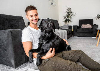 freelancer guy sitting at home working with a dog in an embrace, black labrador.