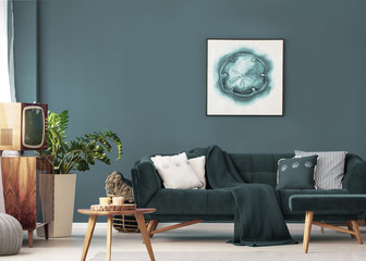 Poster above sofa with pillows in modern living room interior with wooden table and plant. Real photo